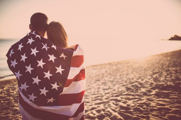 couple with American flag on the beach
