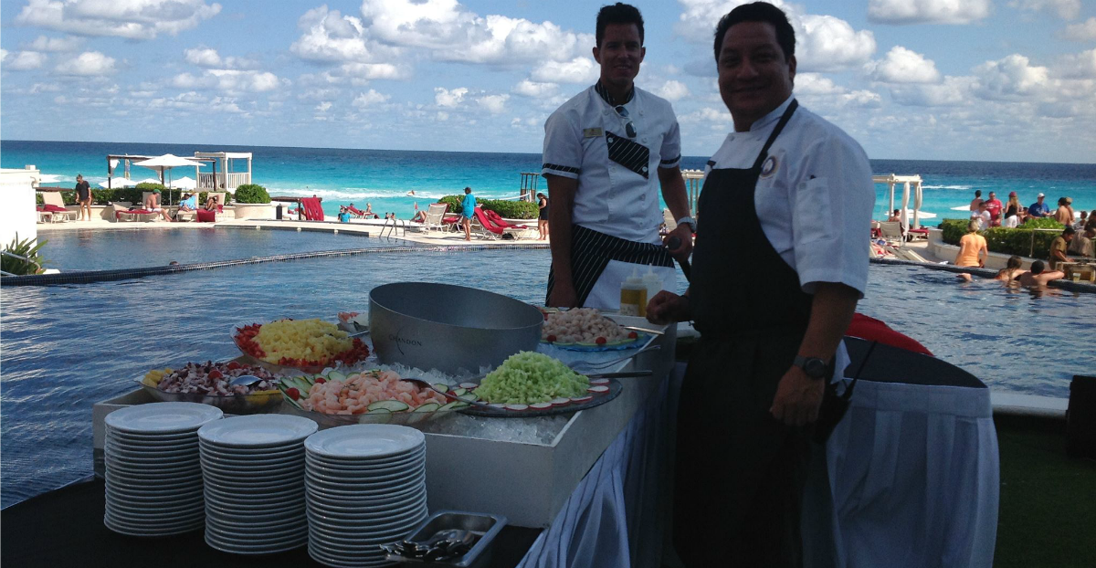 Chefs preparing food by a pool